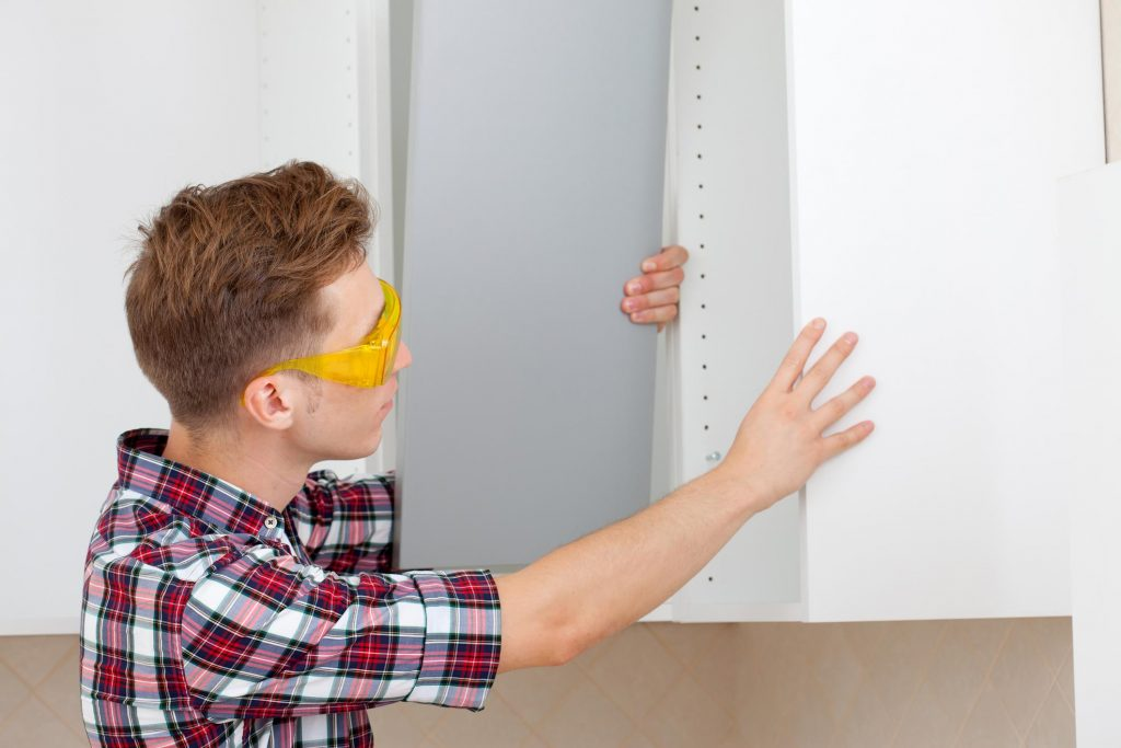 man installing a cabinet