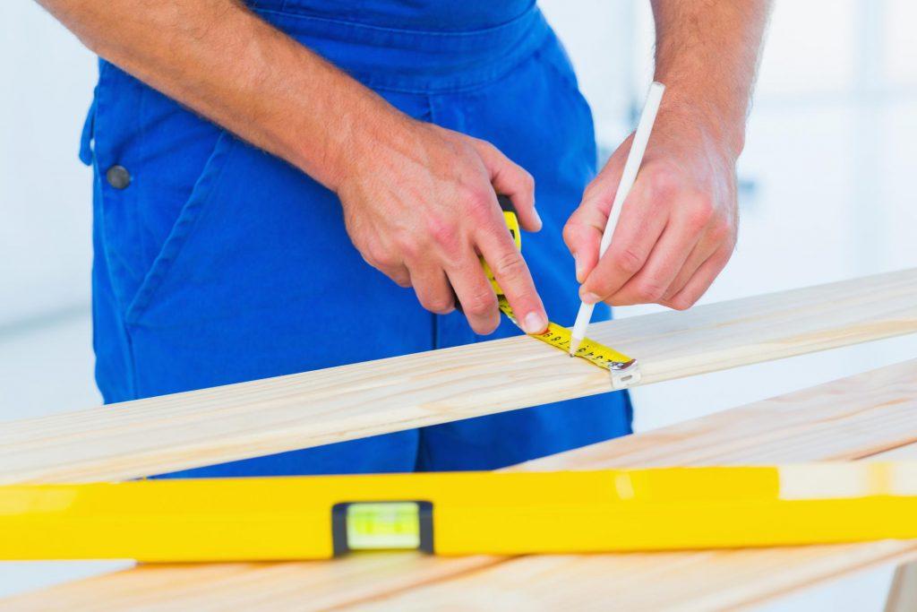 man measuring the wood